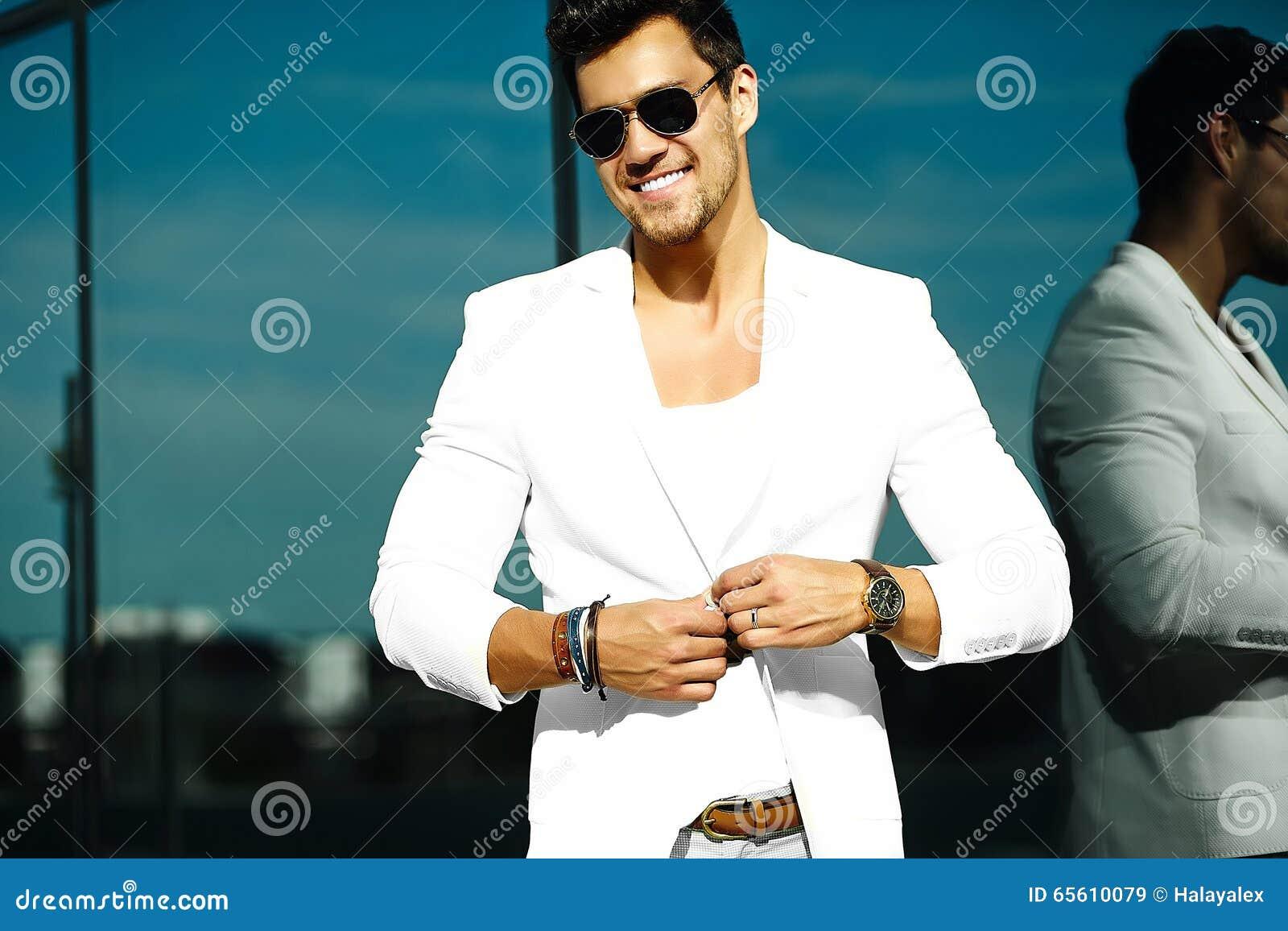 842a1e1ea7590 Forme el retrato del hombre modelo hermoso atractivo joven en traje blanco  casual en gafas de sol en el traje blanco en la calle