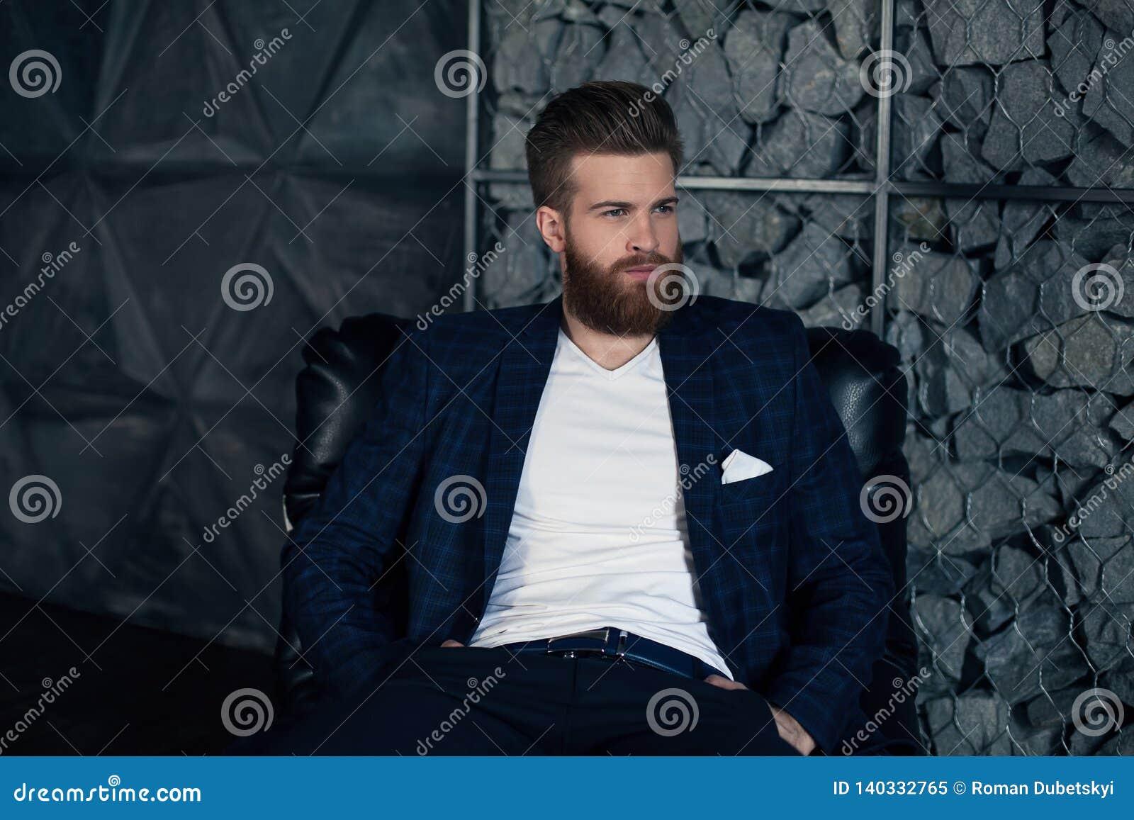 Hombre moderno joven pensativo que se sienta en la butaca