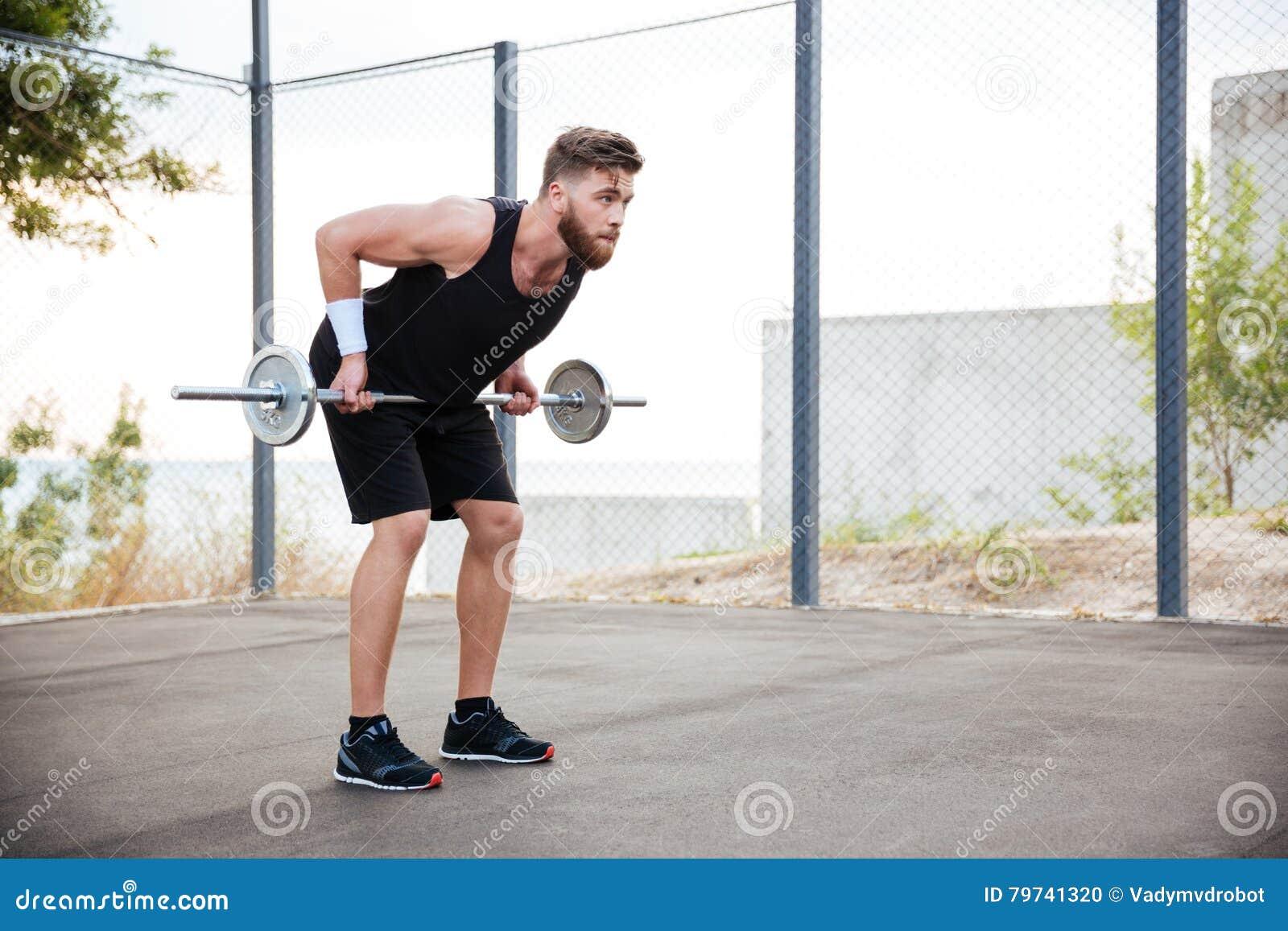 Hombre muscular de la aptitud que hace ejercicio pesado usando barbell