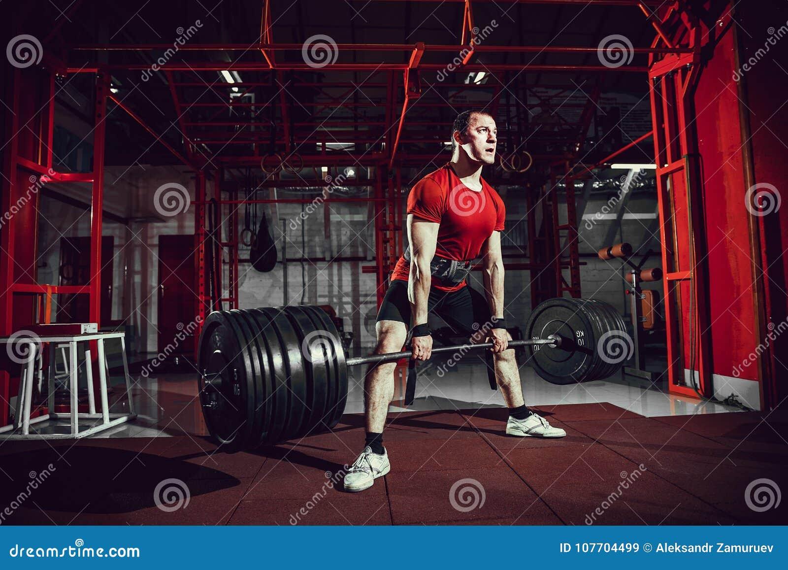 Hombre muscular de la aptitud que hace el deadlift un barbell en centro de aptitud moderno Entrenamiento funcional