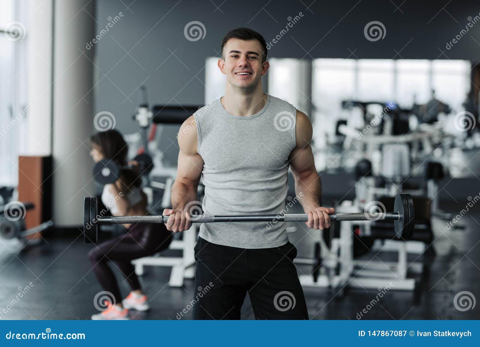Hombre muscular hermoso que se resuelve con pesas de gimnasia en el gimnasio