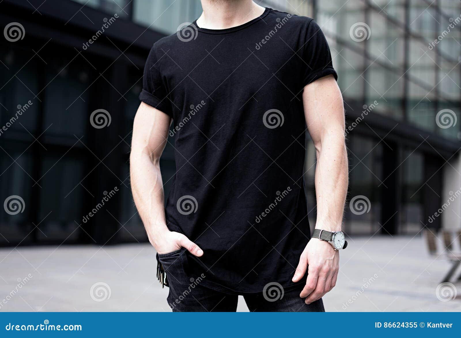 Hombre muscular joven que lleva la camiseta negra y vaqueros que presentan en el centro de ciudad moderna Fondo enmascarado Maque