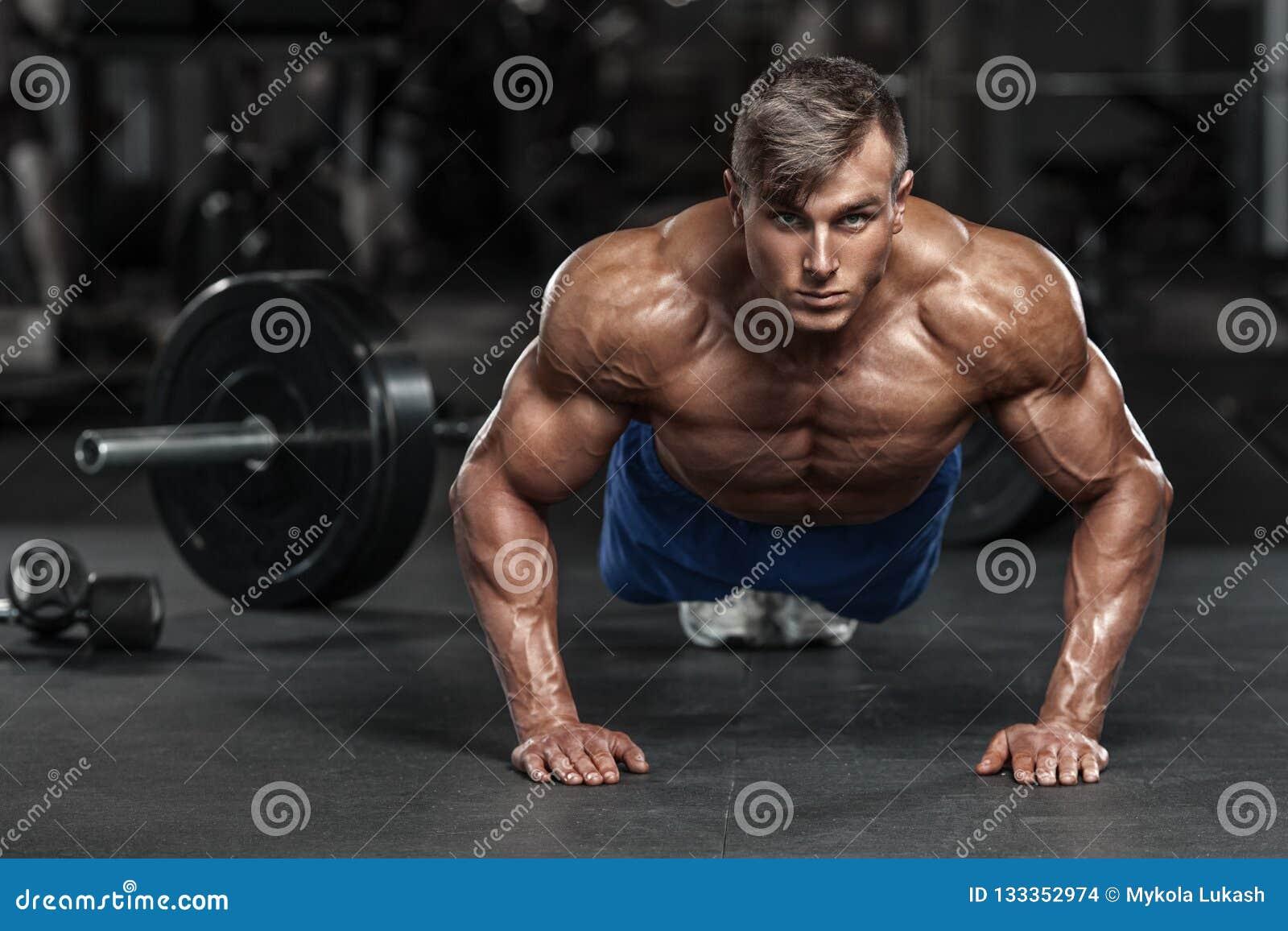 Hombre muscular que se resuelve en el gimnasio que hace los ejercicios de los pectorales, ABS desnudo masculino fuerte del torso