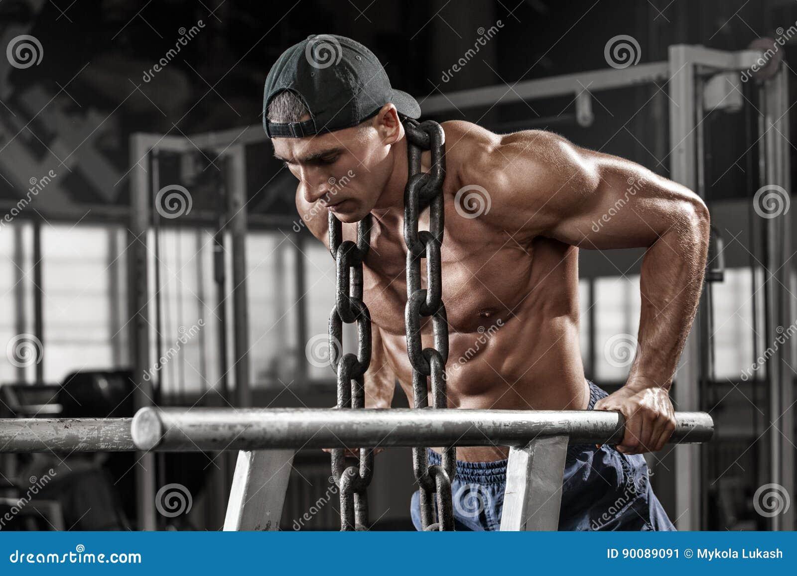 Hombre muscular que se resuelve en el gimnasio que hace ejercicios en barrases paralelas con la cadena, ABS desnudo masculino fue