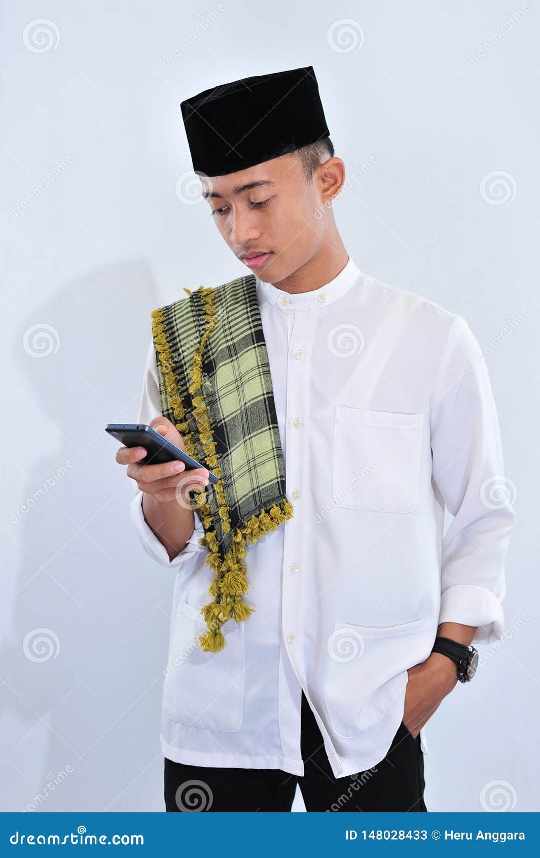 Hombre musulmán asiático feliz usando un teléfono elegante