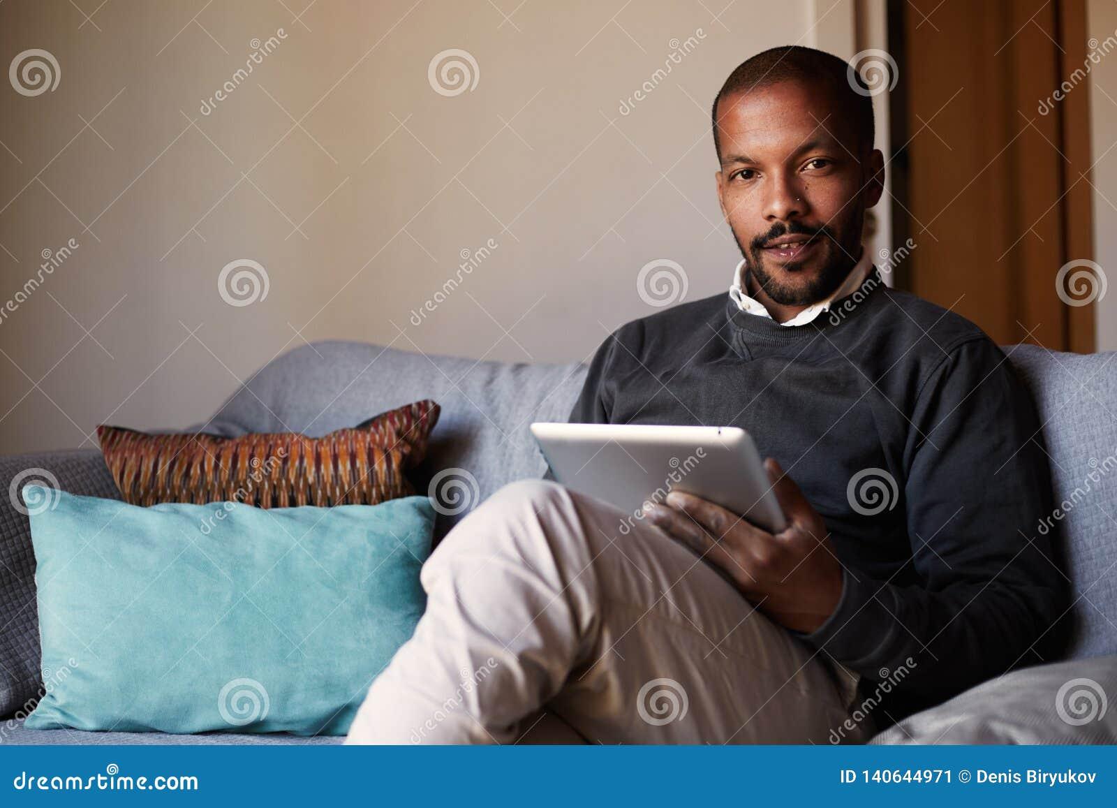 Hombre negro africano hermoso usando la tableta en el sofá del sofá en la sala de estar casera