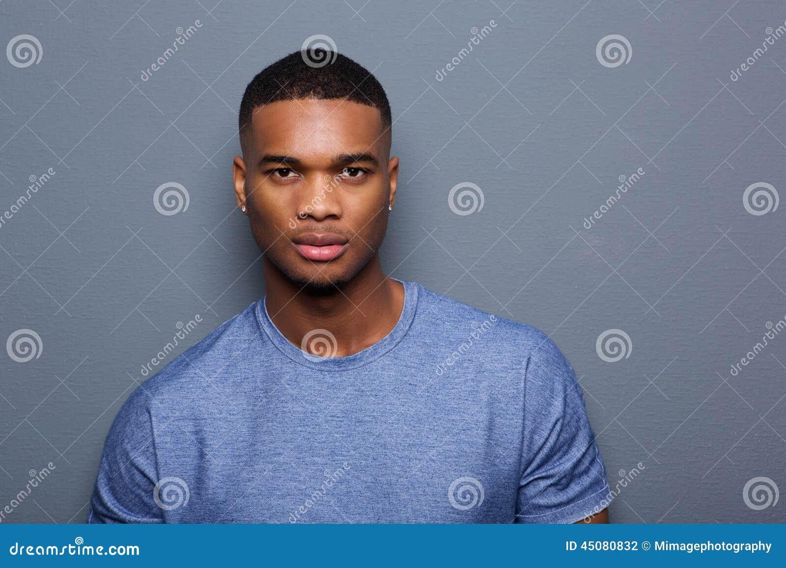Hombre negro joven hermoso con la expresión seria en cara