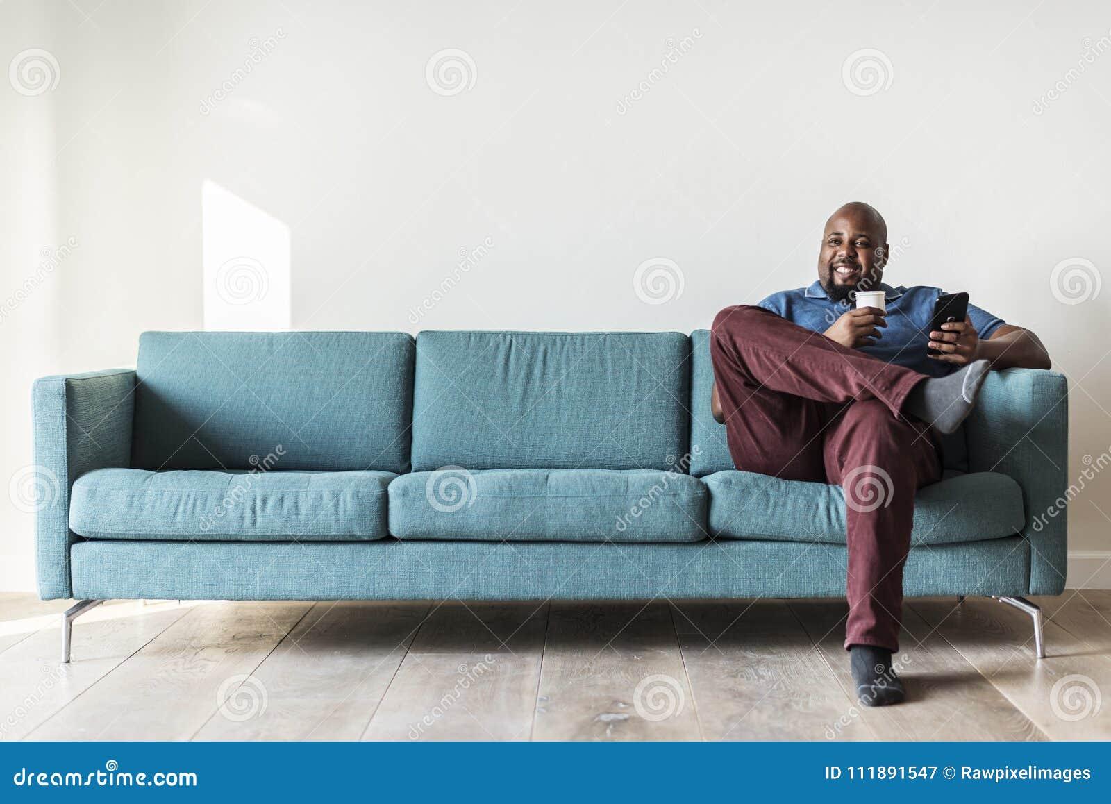 Hombre negro que usa el teléfono móvil en el sofá