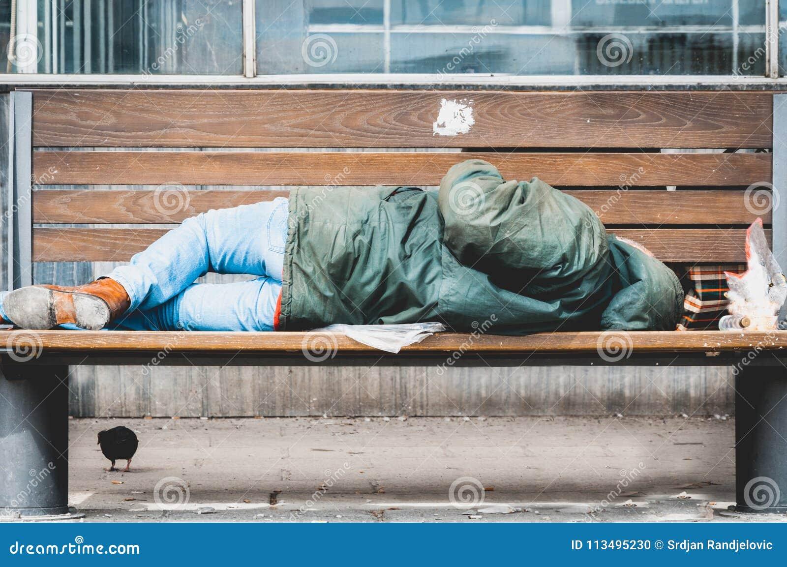 Hombre o refugiado sin hogar pobre que duerme en el banco de madera en la calle urbana en la ciudad, concepto documental social