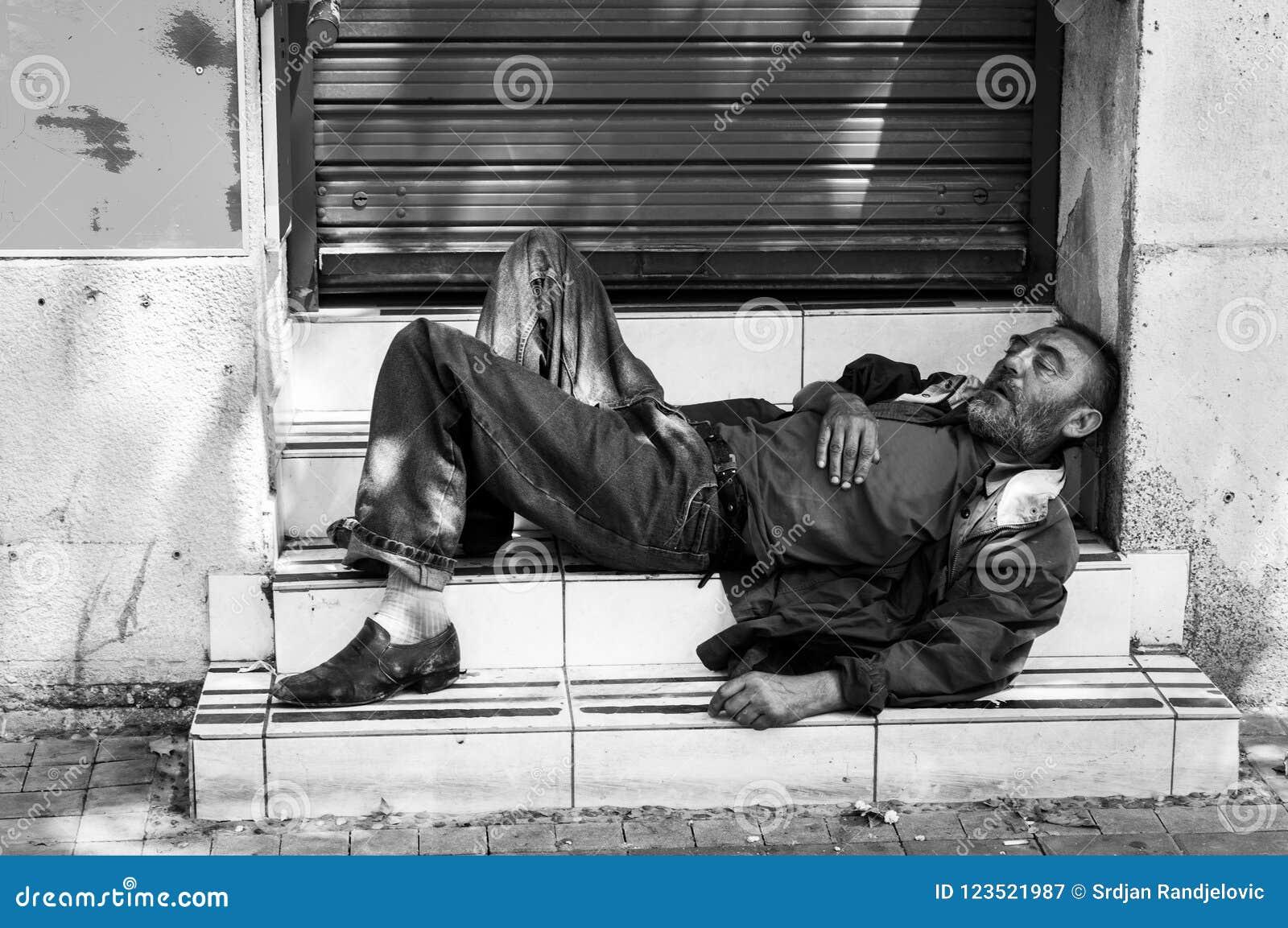 Hombre o refugiado sin hogar pobre que duerme en las escaleras en la calle, concepto documental social blanco y negro
