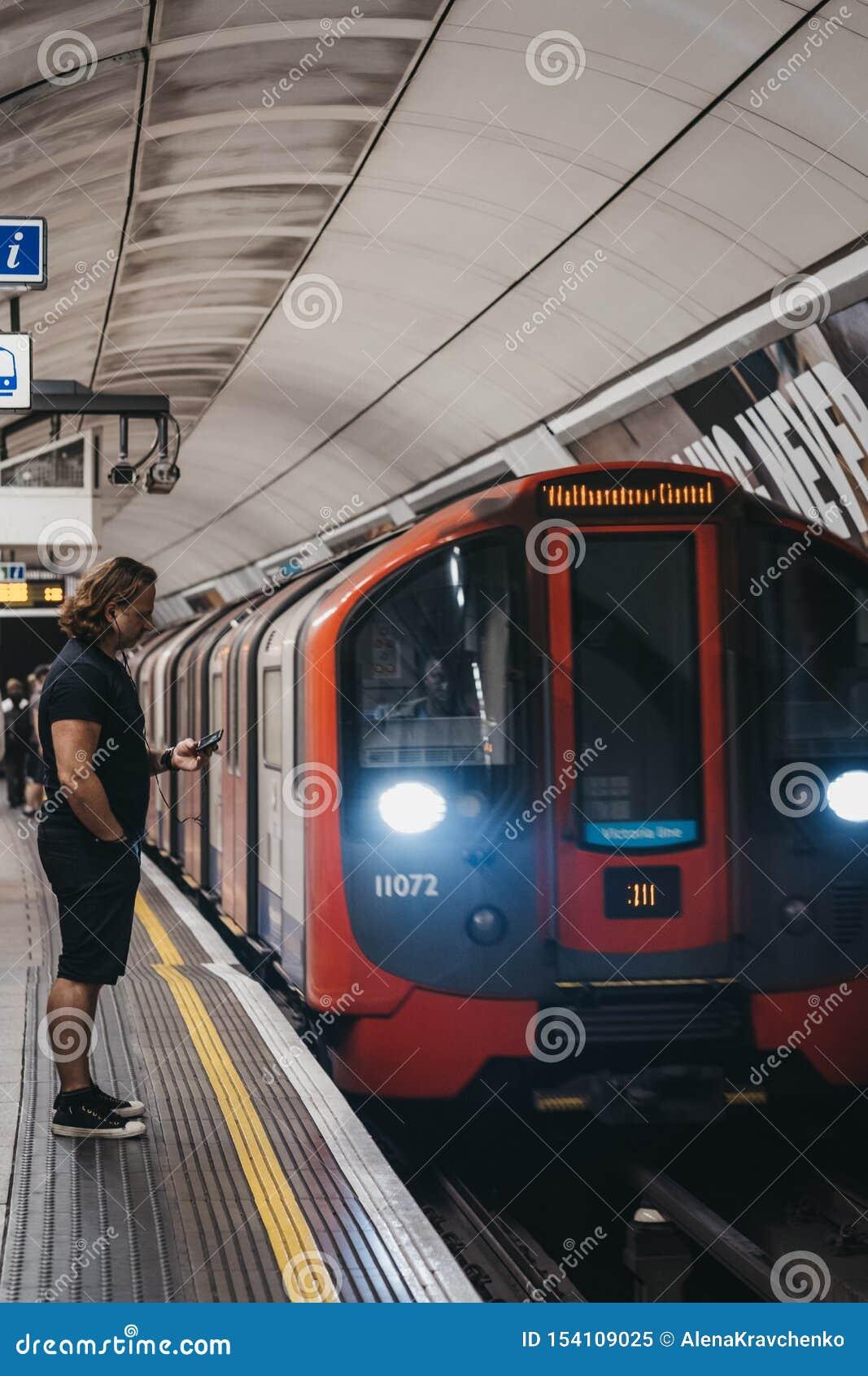 Hombre Parado En Una Plataforma De La Estación Del Metro De Londres Usando Su Teléfono Tren Pasando Por Ahí Movimiento Borroso Imagen Editorial Imagen De Ahí Teléfono 154109025