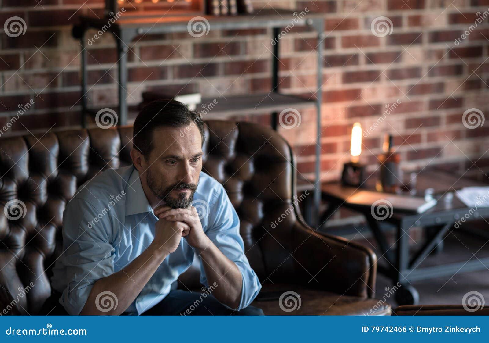Hombre pensativo agradable que se sostiene la barbilla