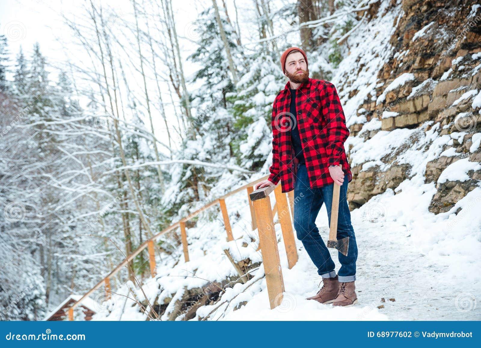 Hombre pensativo con la barba que sostiene el hacha en las montañas en invierno