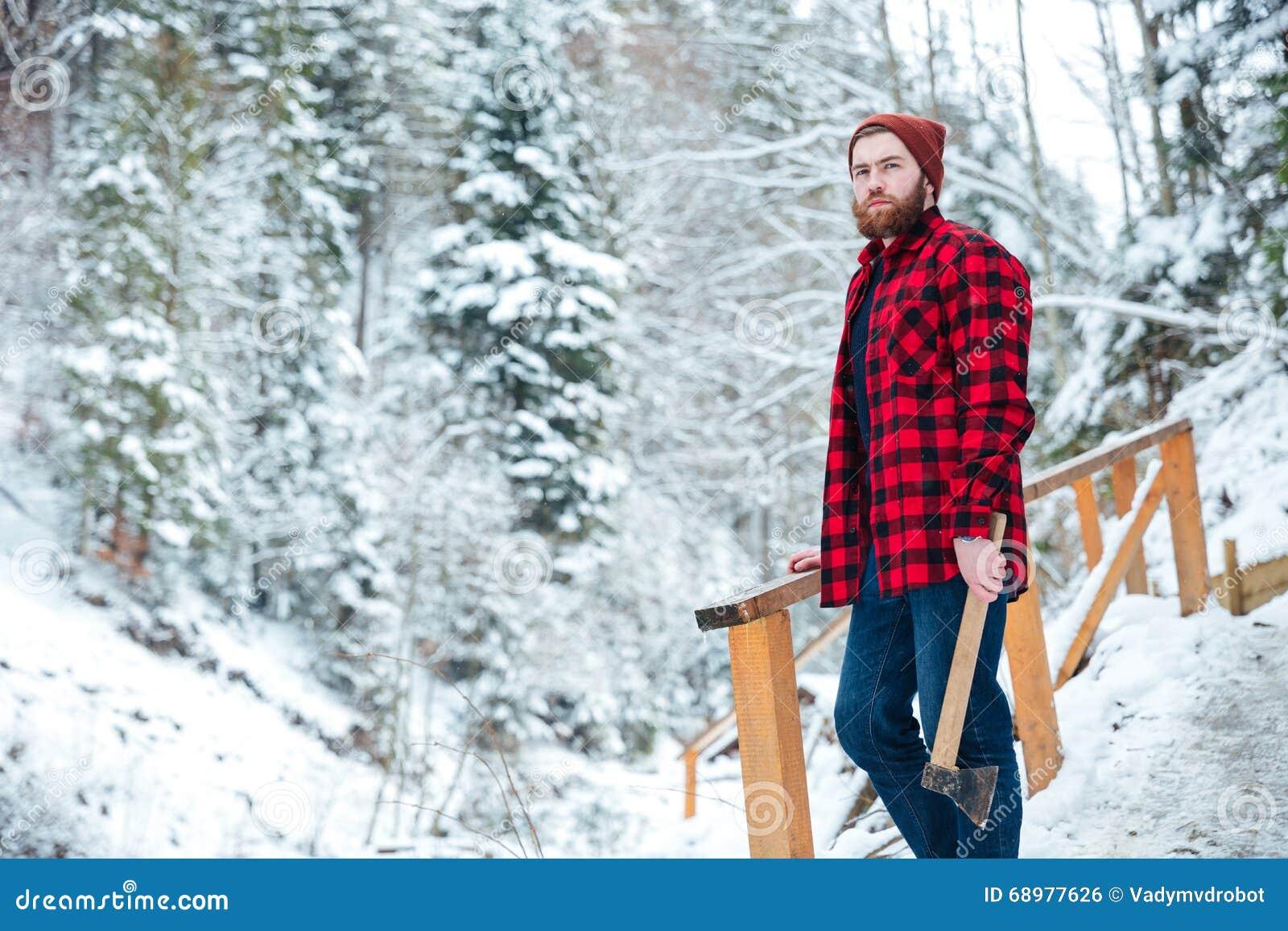 Hombre pensativo hermoso con el hacha que se coloca en bosque del invierno de la montaña