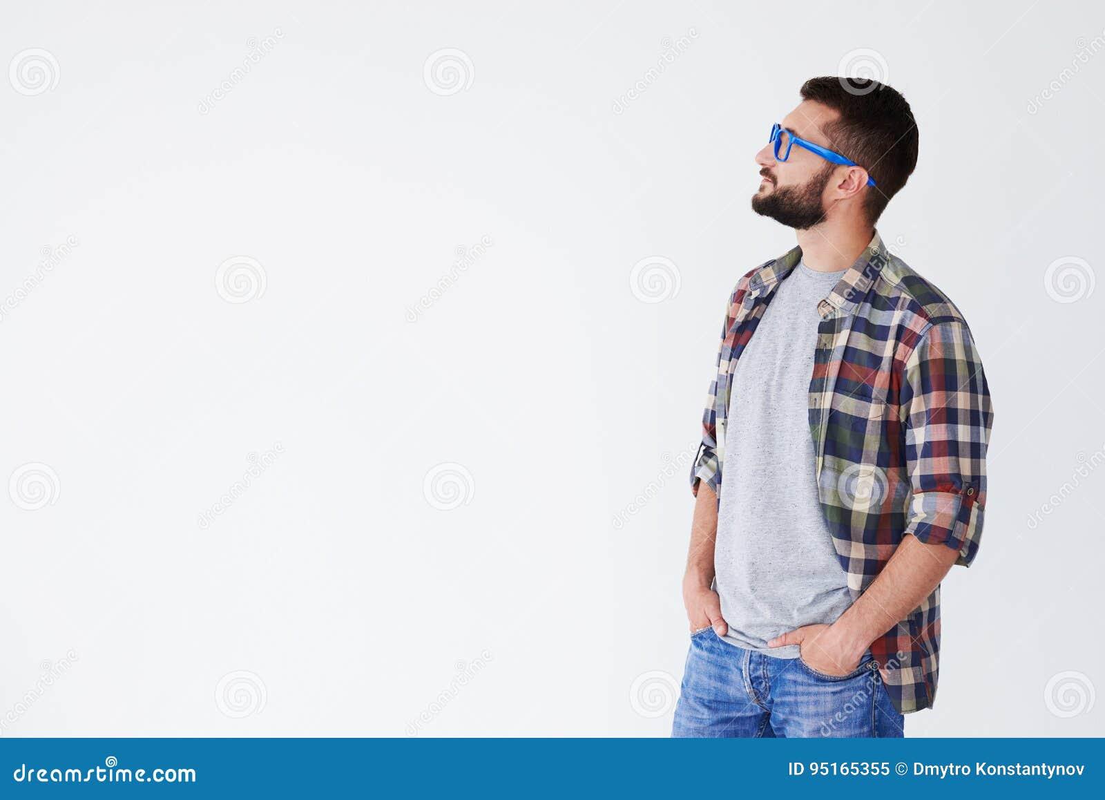 Hombre pensativo que lleva a cabo las manos en los bolsillos que miran el espacio de la copia