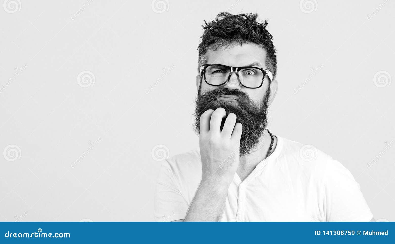 Hombre pensativo que toca su barba en la pared blanca El hombre hermoso en vidrios piensa El individuo barbudo emocional tiene un