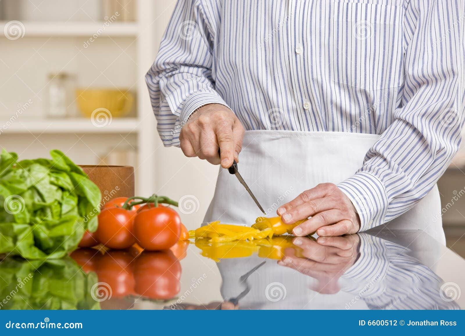 Hombre provechoso que prepara la ensalada en cocina