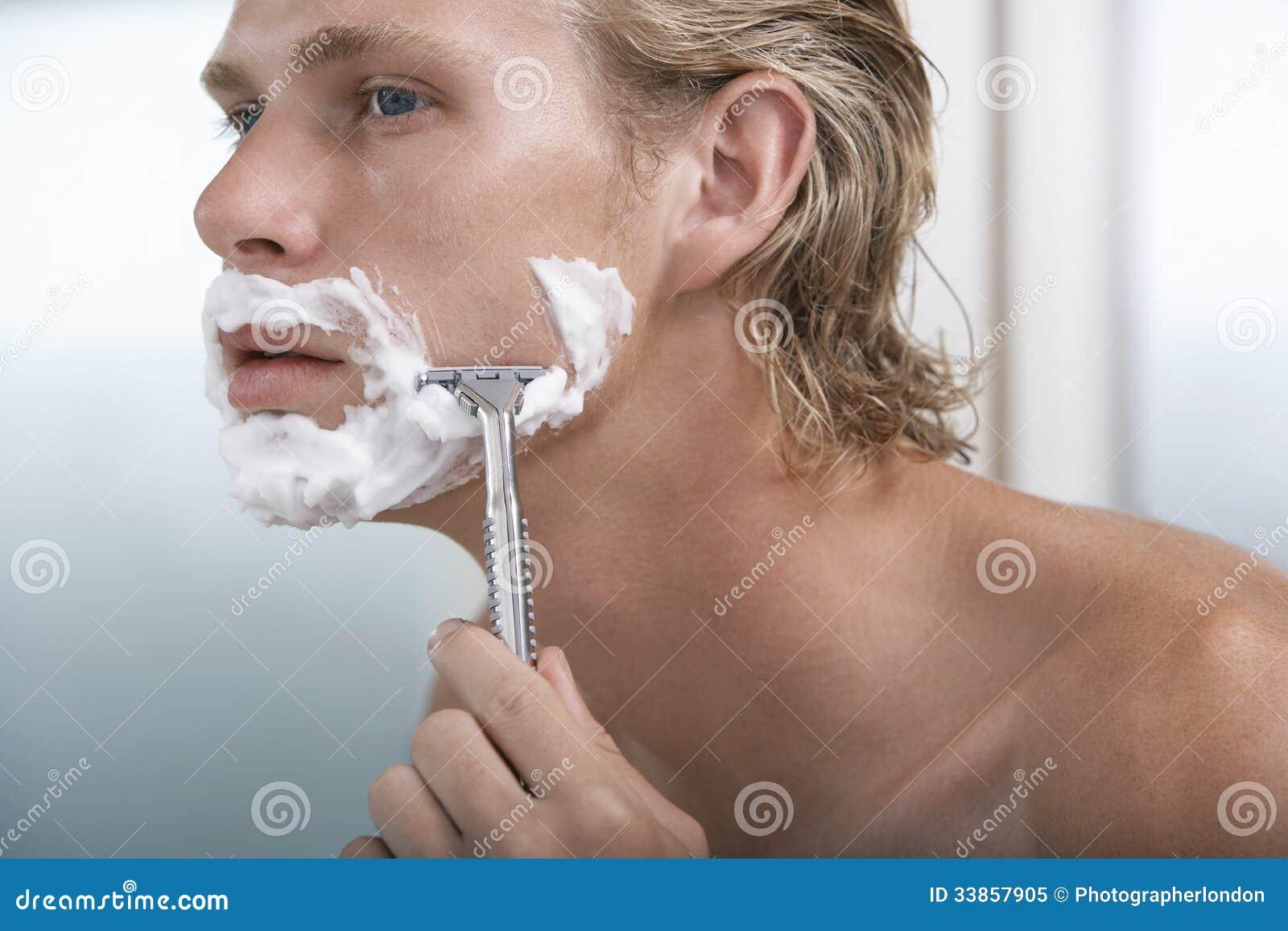 Hombre que afeita en cuarto de baño