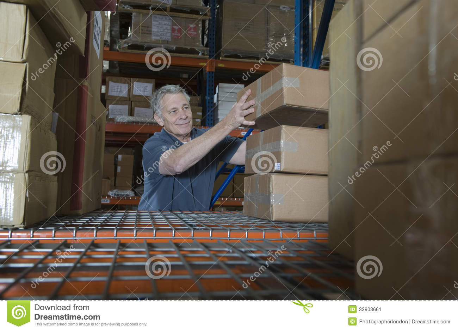 Hombre que apila las cajas en Warehouse