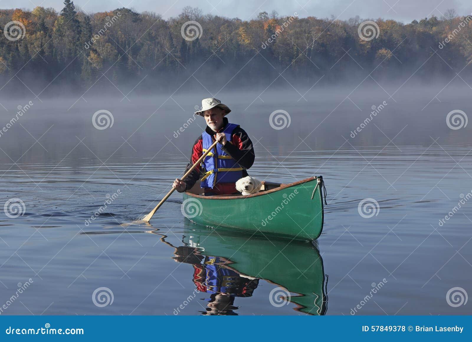Hombre que bate una canoa con un pequeño perro blanco en el arco