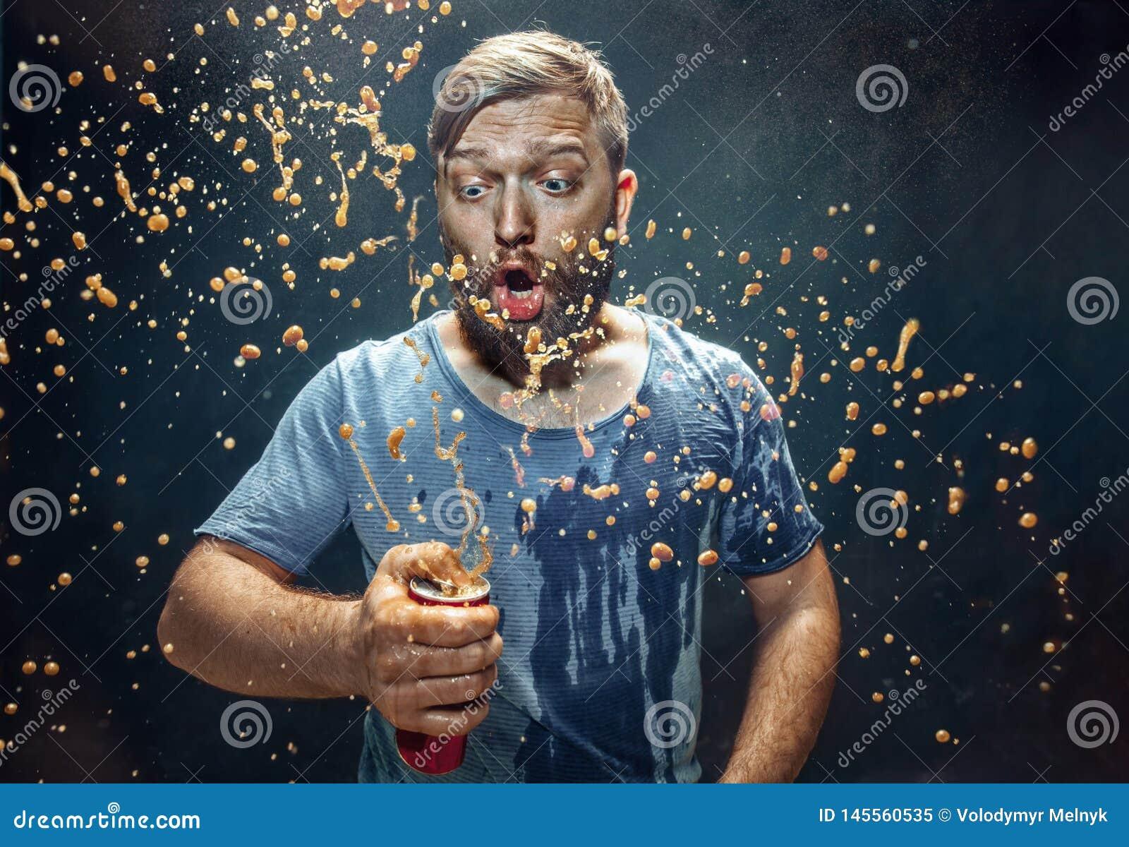 Hombre que bebe una cola y que disfruta del espray