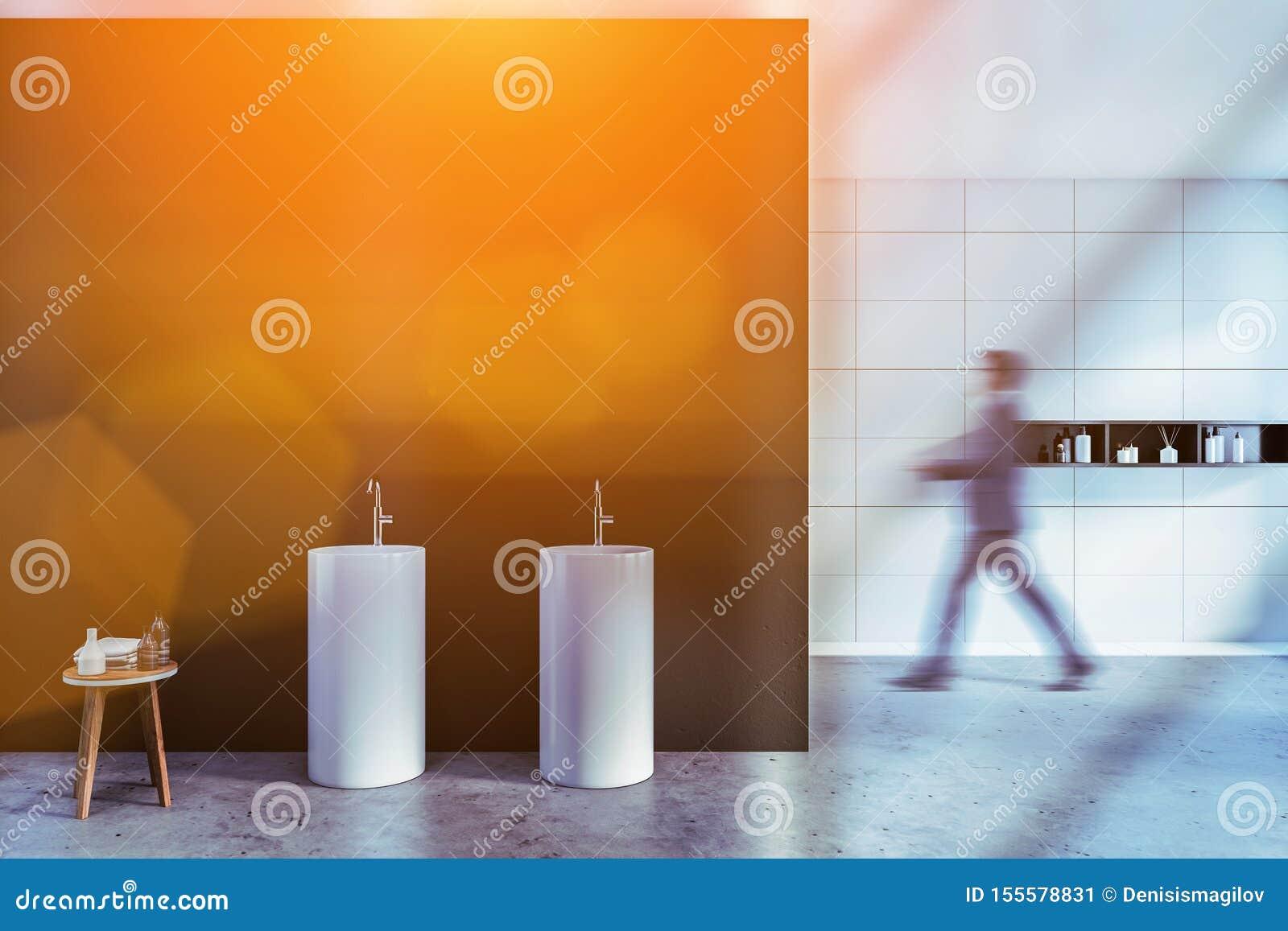 Hombre que camina en cuarto de baño espacioso del balneario con el fregadero