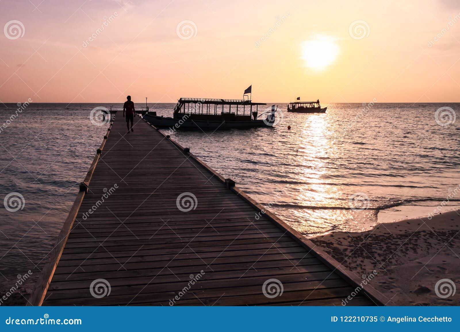 Hombre que camina en el embarcadero en la puesta del sol en el centro turístico isleño de Maldivas