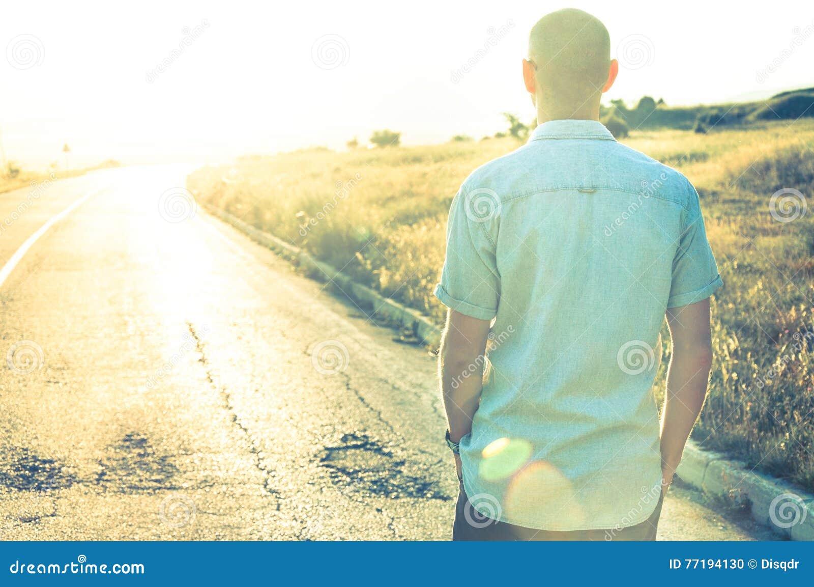 Hombre que camina en puesta del sol en el camino vacío