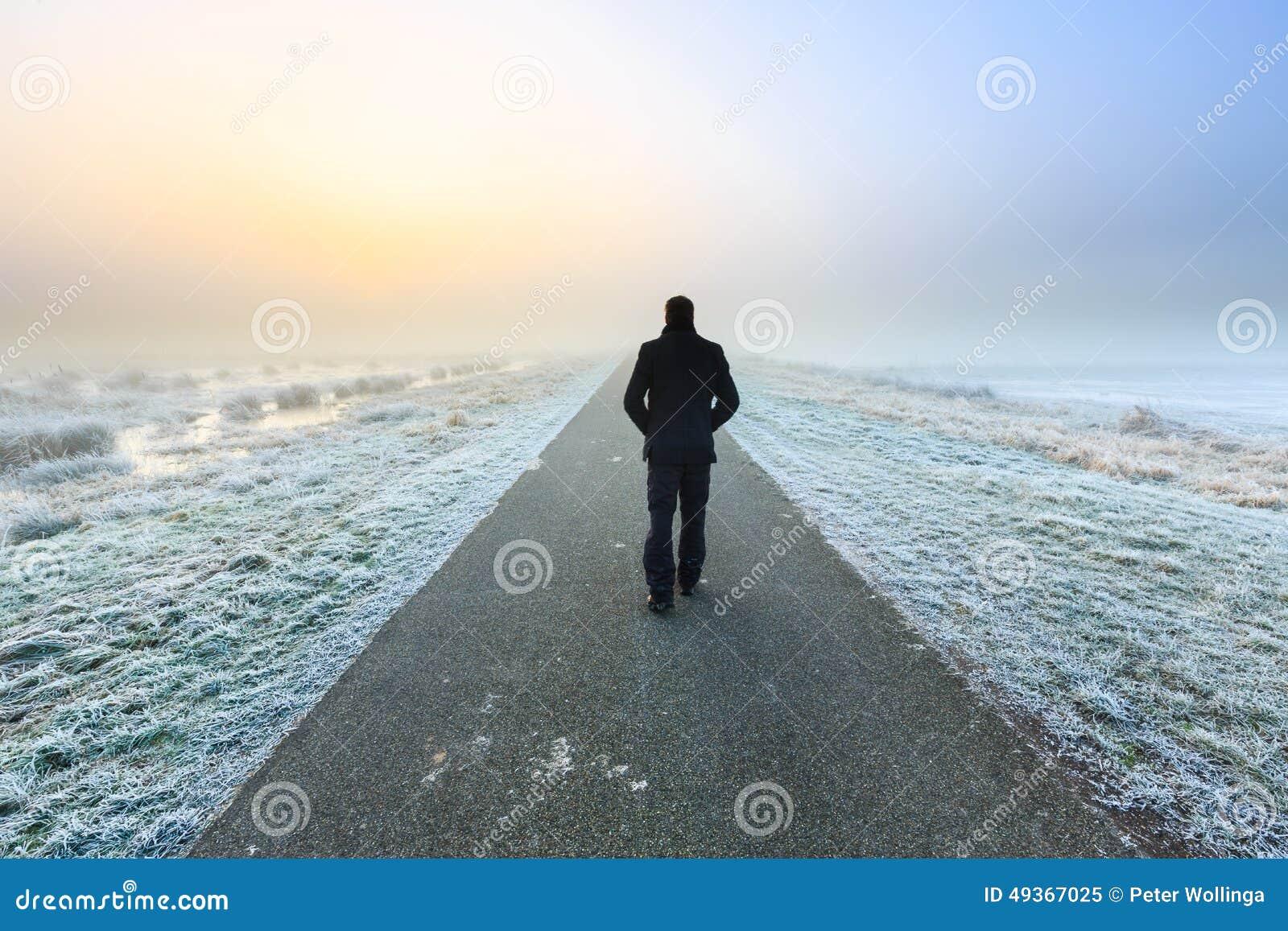 Hombre que camina en un raod solitario vacío