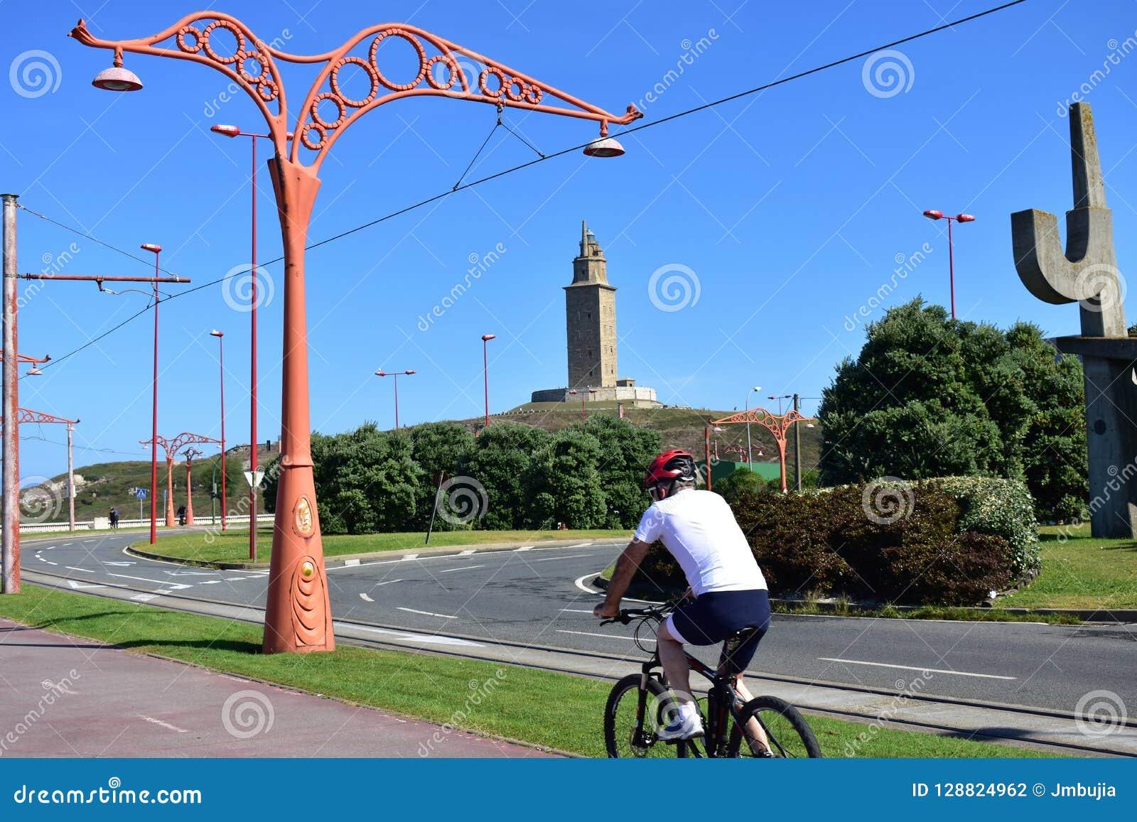 Hombre que completa un ciclo en una  promenade  Ninguna cara, gente irreconocible Parque público, árboles y camino Cielo azul, dí