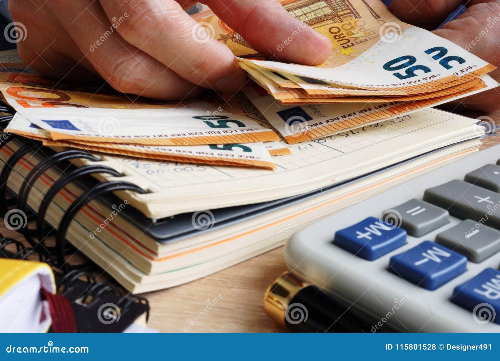 Hombre que cuenta billetes de banco euro Escritorio con la calculadora, el libro mayor y euros
