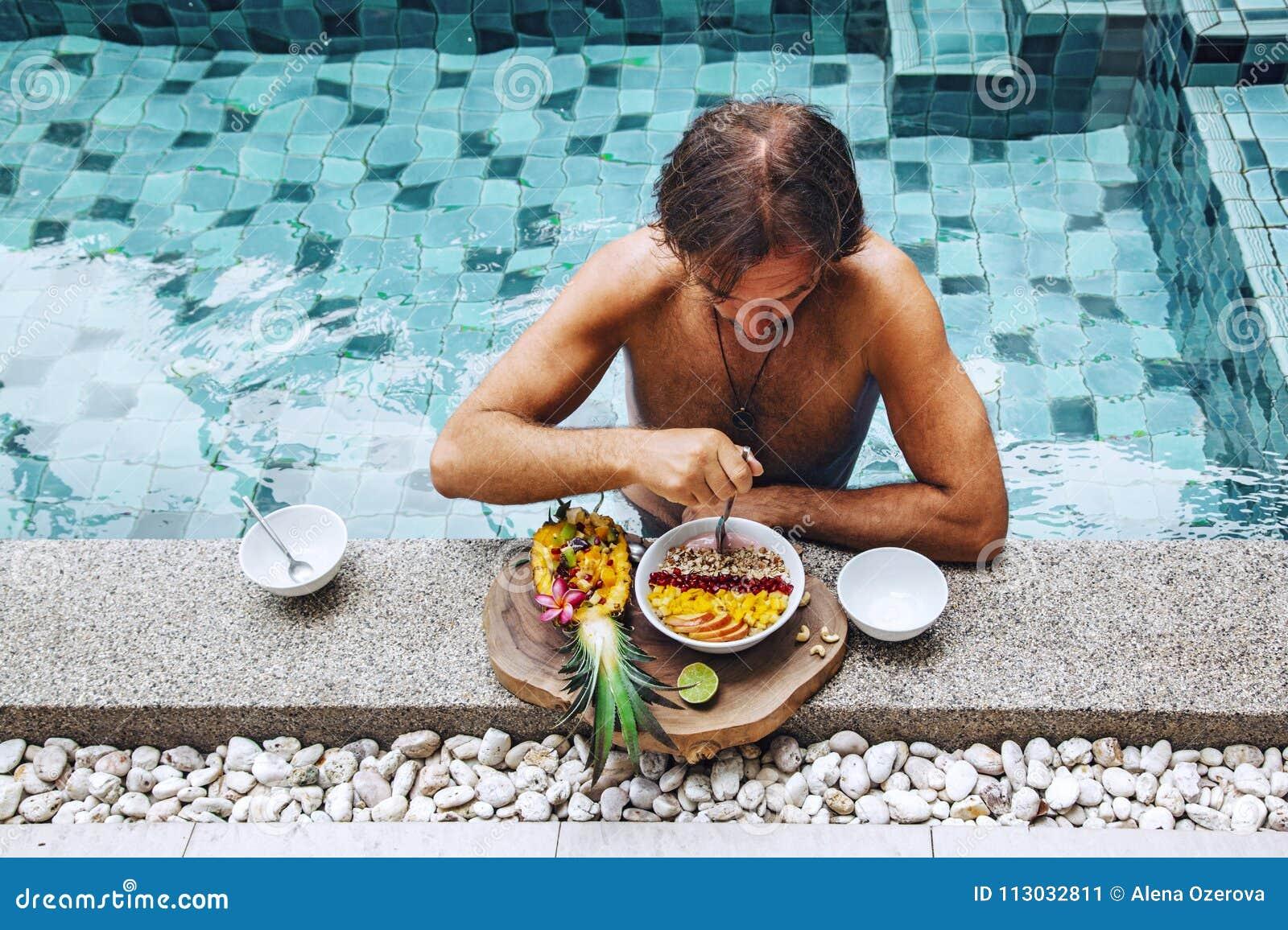 Hombre que desayuna en la piscina