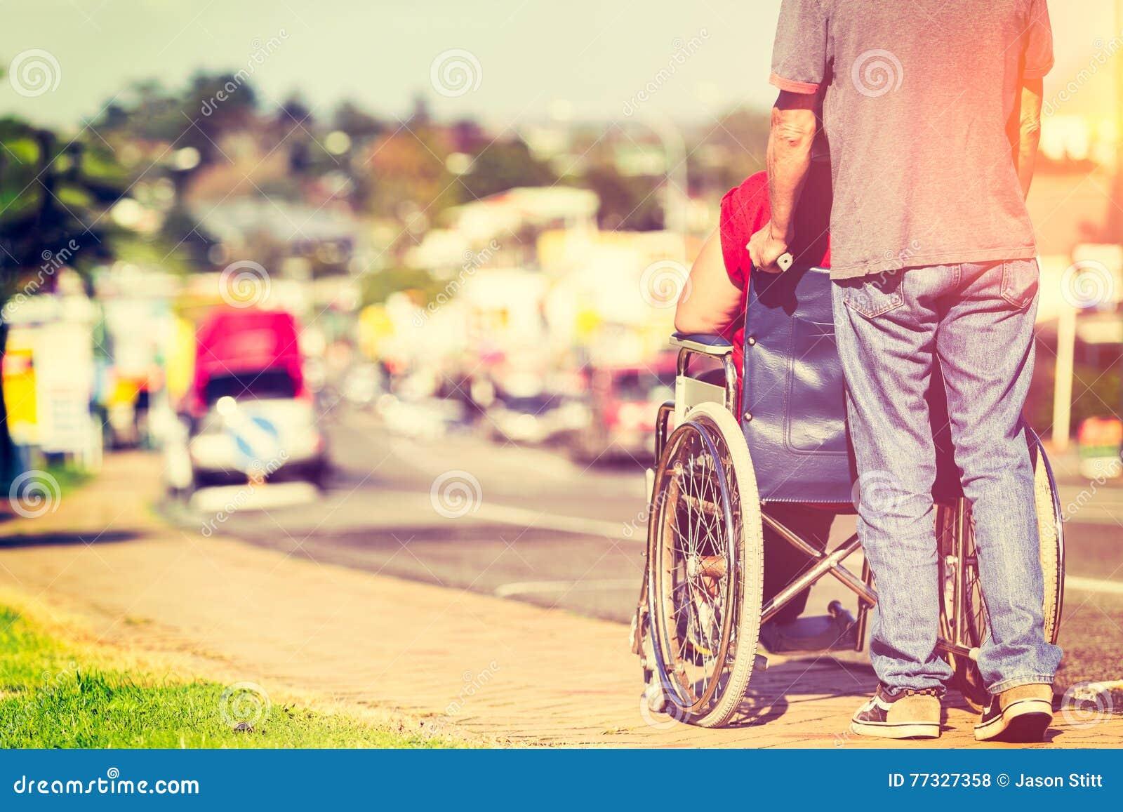 Hombre que empuja el sillón de ruedas