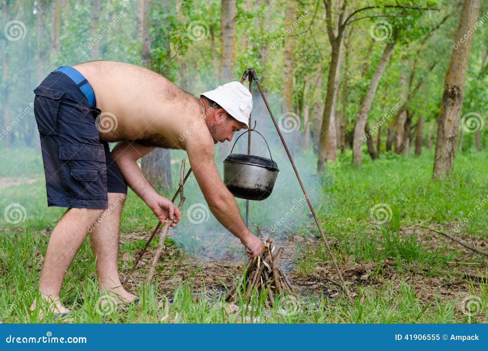Hombre que enciende un fuego de cocinar mientras que acampa