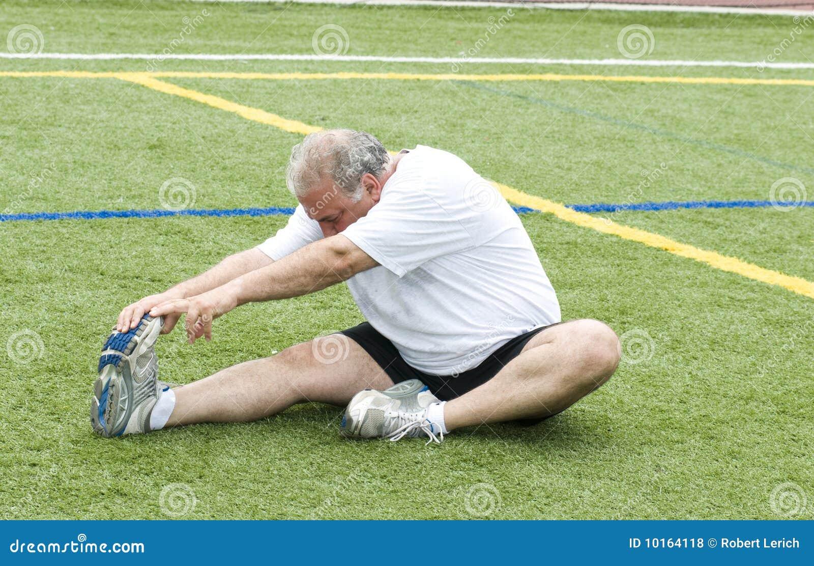 Hombre que estira ejercitando el campo