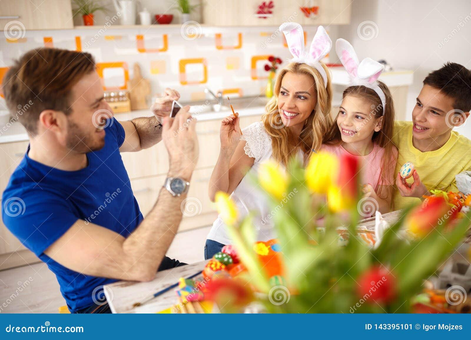 Hombre que fotografía a la familia mientras que pinta los huevos