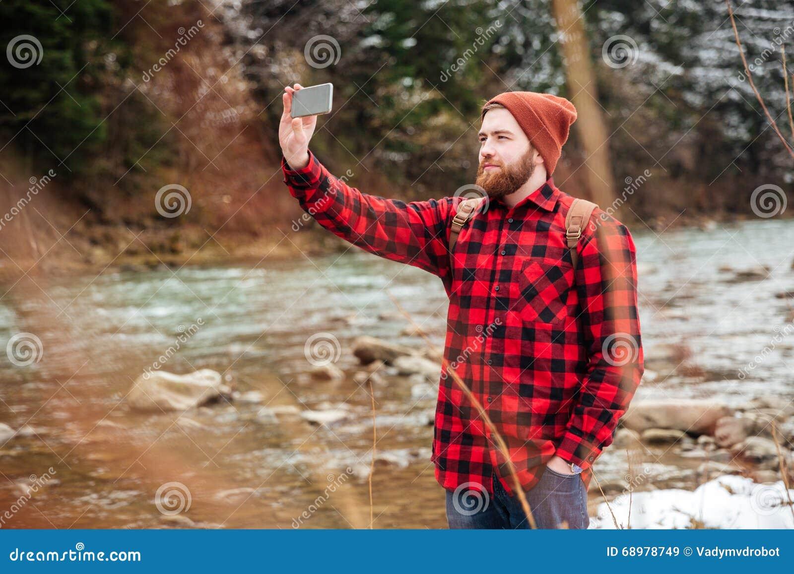 Hombre que hace la foto en smartphone al aire libre