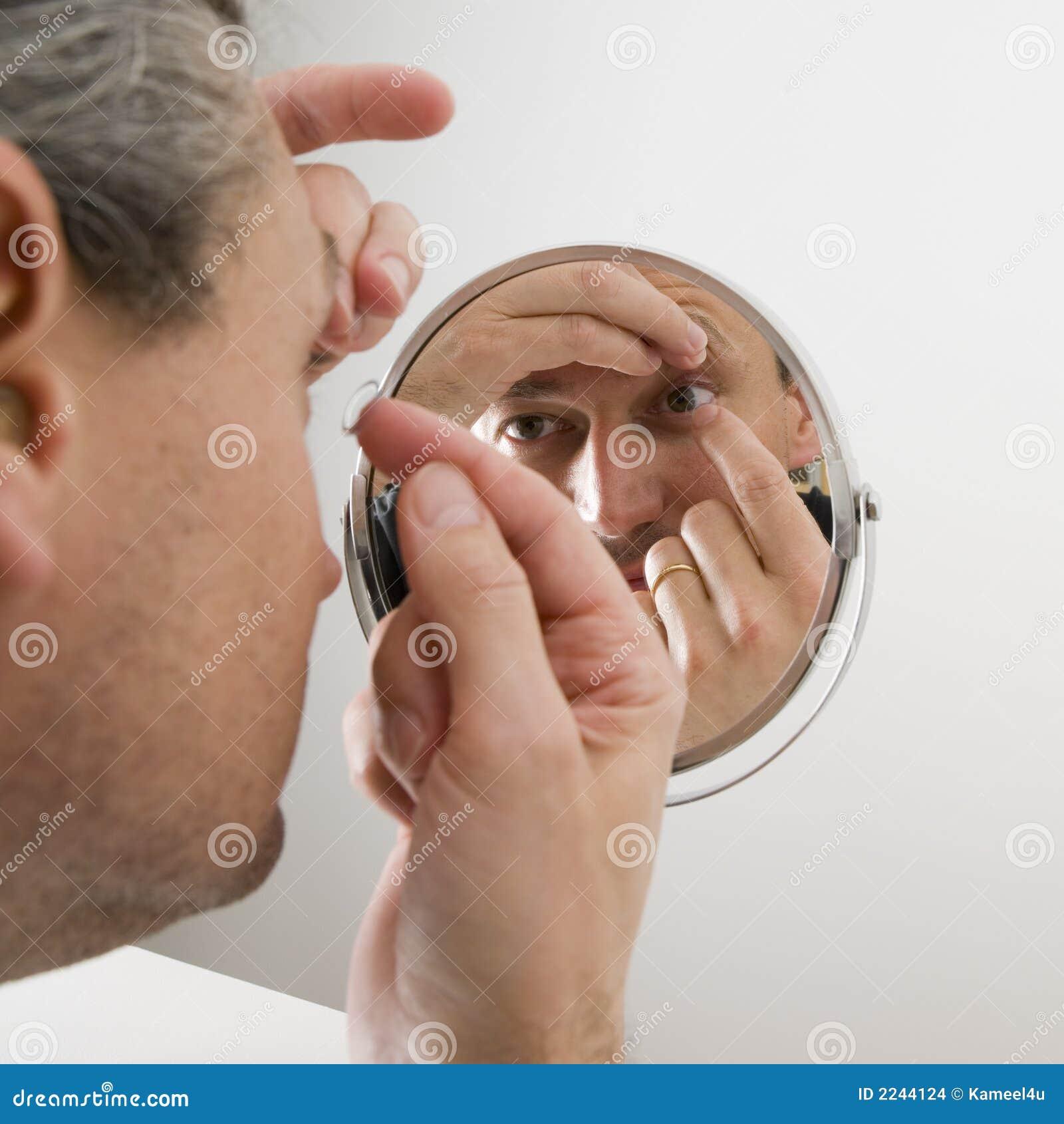 Hombre que inserta una lente de contacto