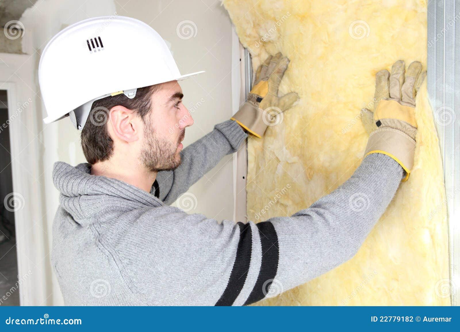Hombre que instala el aislante de la pared