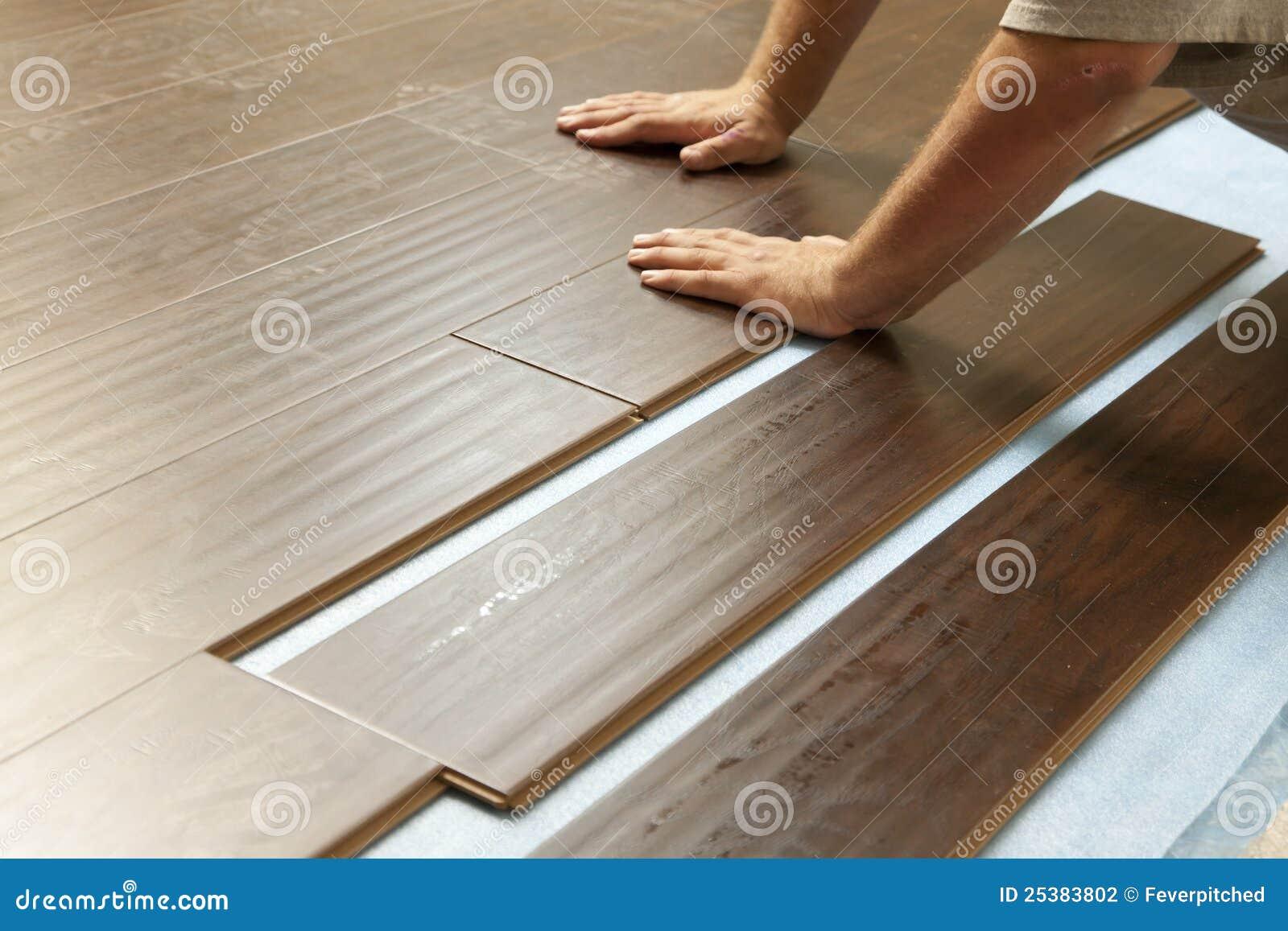 Hombre que instala el nuevo suelo de madera laminado