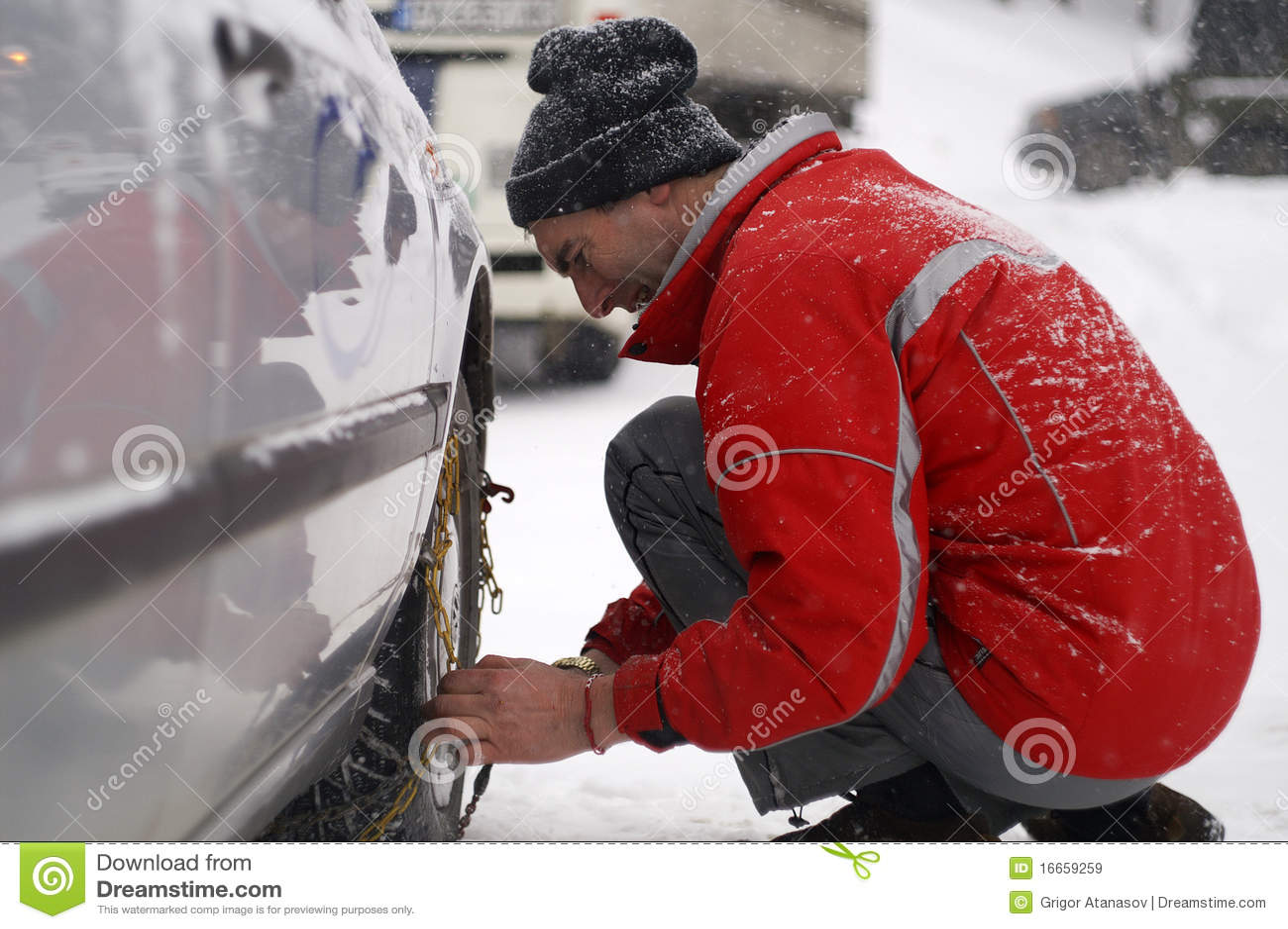 Hombre que instala encadenamientos de nieve