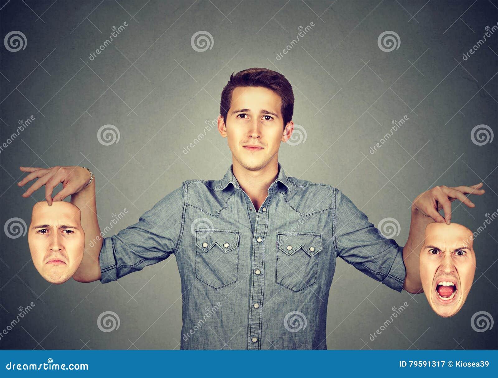Hombre que lleva a cabo dos diversas máscaras de la emoción