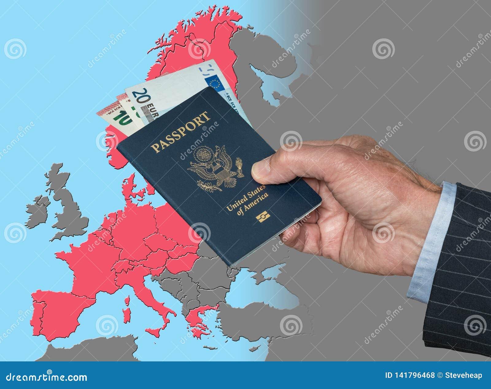 Hombre que lleva a cabo el pasaporte y euros de los E.E.U.U. en el mapa de la zona de Schengen