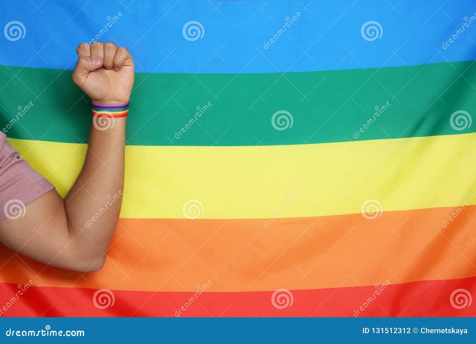 Hombre que lleva pulsera gay a mano cerca de la bandera del arco iris, primer