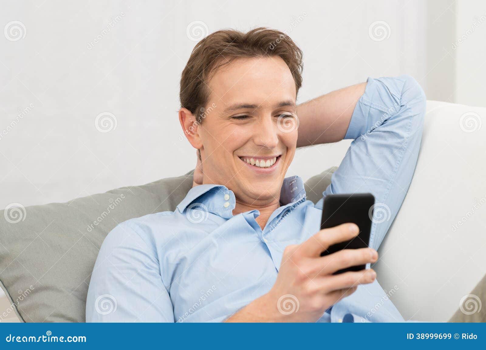 Hombre que miente en Sofa With Cellphone