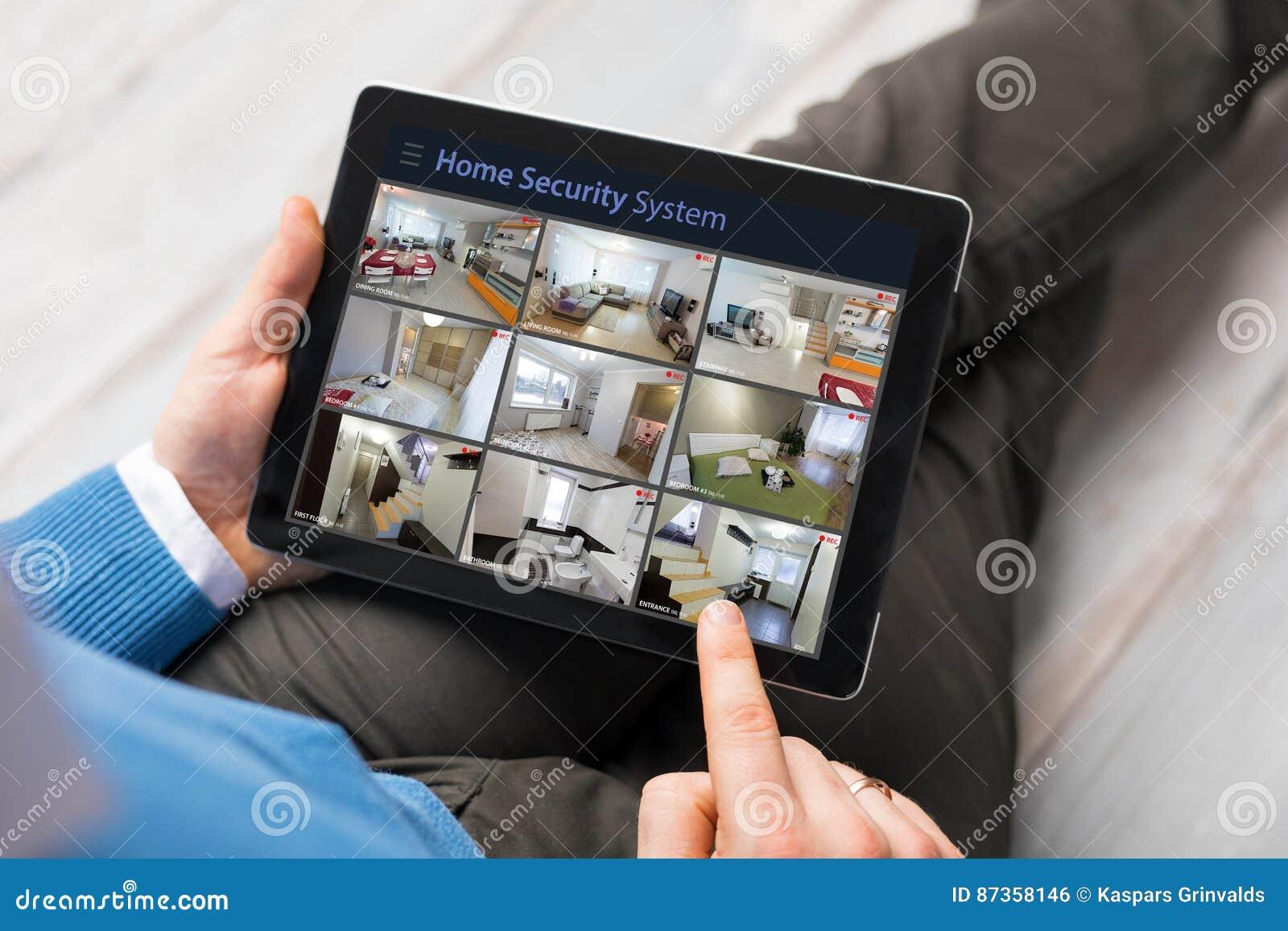 Hombre que mira en casa las cámaras de seguridad en la tableta