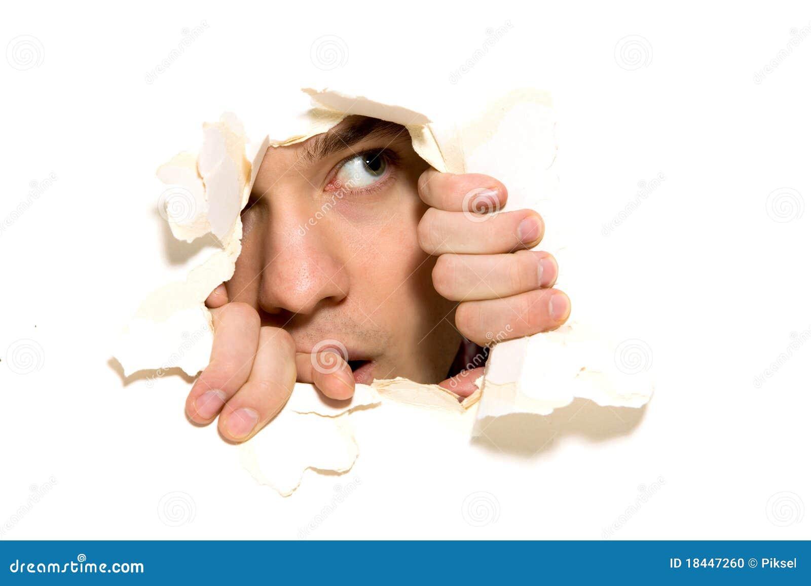 Hombre que mira furtivamente a través del agujero en el papel