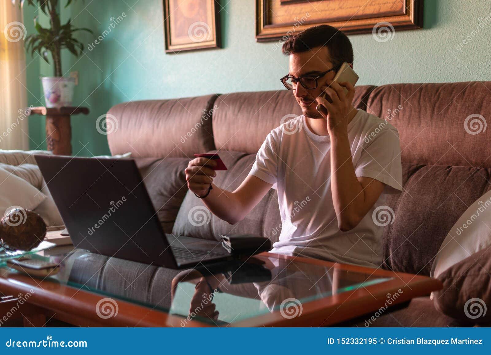Hombre que paga con la tarjeta de crédito en el ordenador portátil en casa