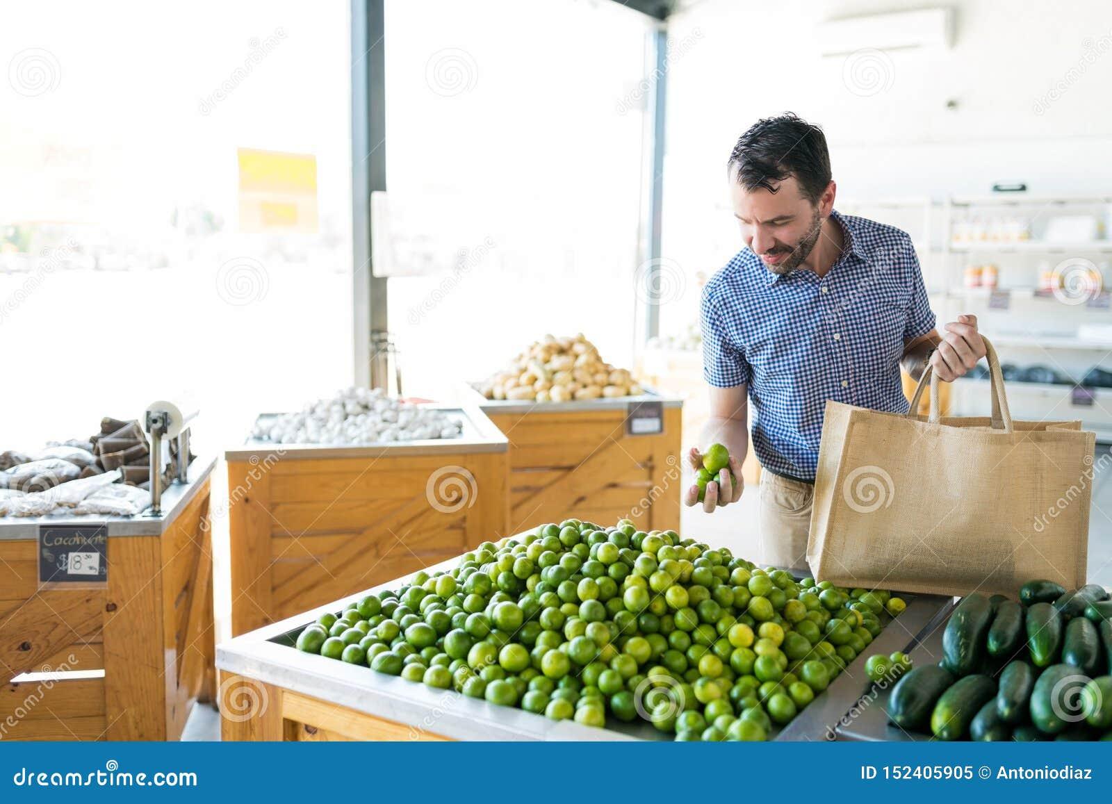 Hombre que recoge los limones saludables del mercado vegetal