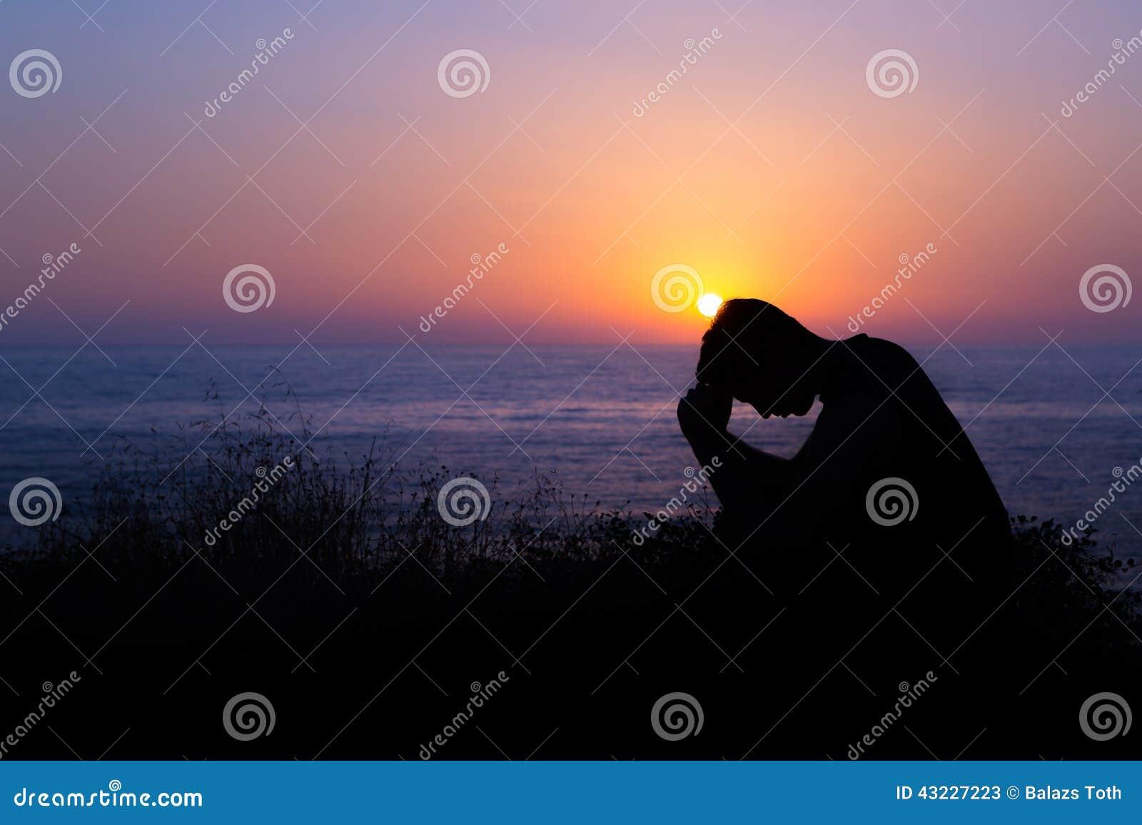 Hombre que ruega por el mar en la puesta del sol